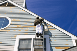 A man climbing a ladder up the side of a house after completing his online ladder safety course