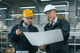 A supervisor looks over his safety plan with an employee