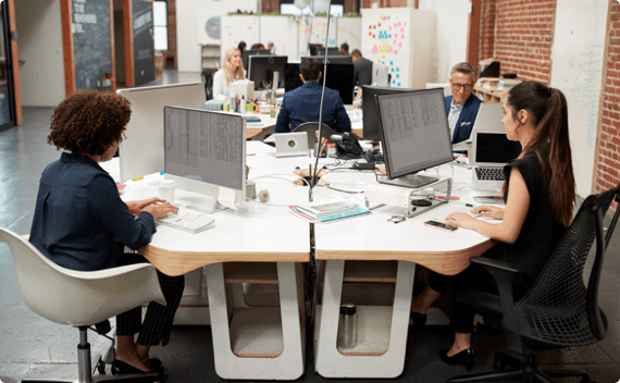 Employees in an open work space working at ergonomically friendly desks