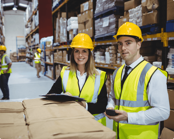 Two employees wearing safety gear smile in the warehouse