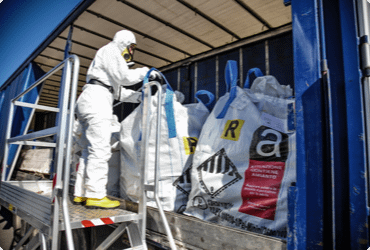 A worker in a hazmat suit handling asbestos