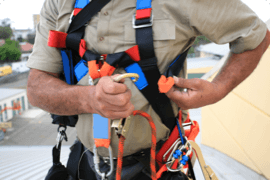 A man wears a fall protection harness after completing his online fall protection course