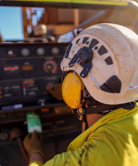 A worker using heavy machinery wears a helmet and earmuffs
