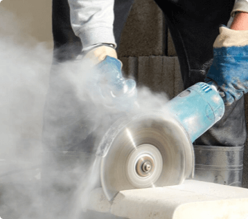 A worker uses a circular saw to cut through concrete