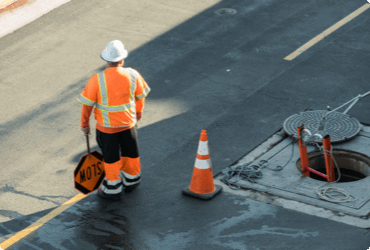 A worker control traffic next to an open manhole