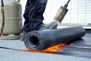 A worker uses propane on a construction site to lay down flooring