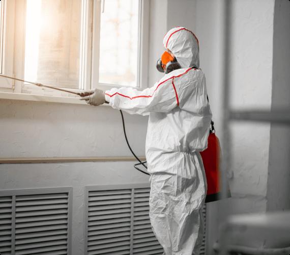A worker in a hazmat suit performs environmental sampling