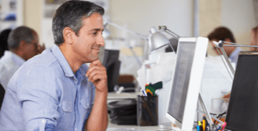 A smiling employee working at an ergonomically friendly desk