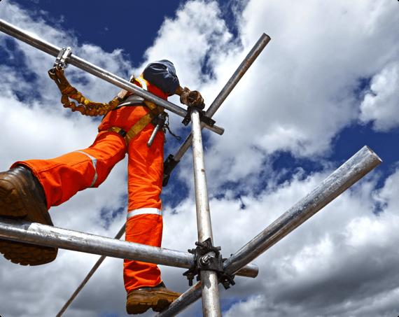 A construction worker walks on scaffolding