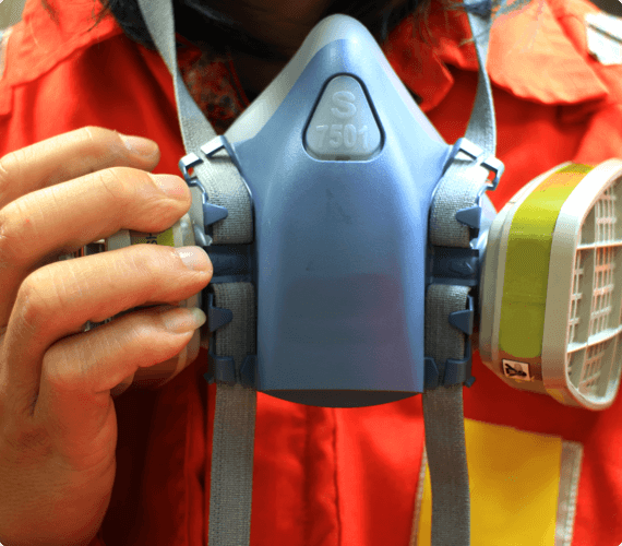 A workplace inspector puts on a respirator