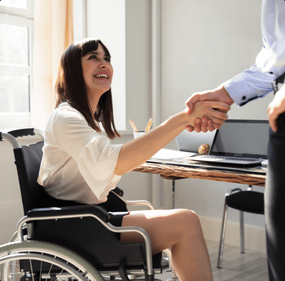 A woman in a wheelchair shakes hands with a man