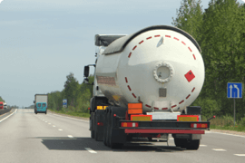 A truck drives down the highway carrying a dangerous load.