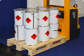 A dozen buckets marked flammable on a wooden pallet carried by a forklift