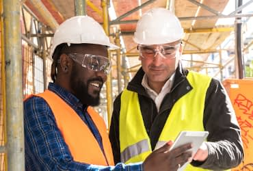 Members of a joint health and safety committee smile as they review safety procedures onsite