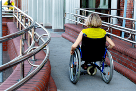 A woman in a wheelchair enters a building on an accessible ramp