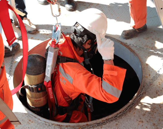 a worker with a harness is lowered into a confined space