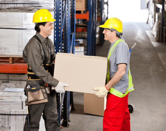 Two employees carry a heavy box together