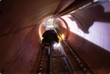 A worker moves through a confined space after completing their confined space awareness training