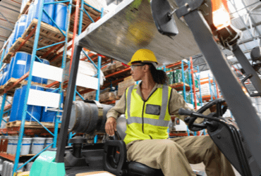 An employee reverses a forklift after taking the forklift refresher course