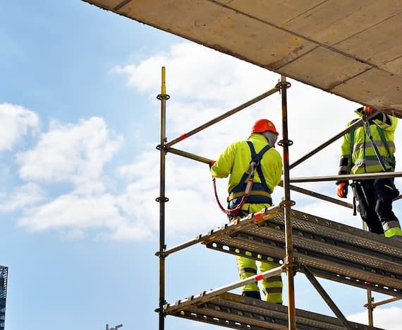 Two workers wearing fall protection equipment work on scaffolding