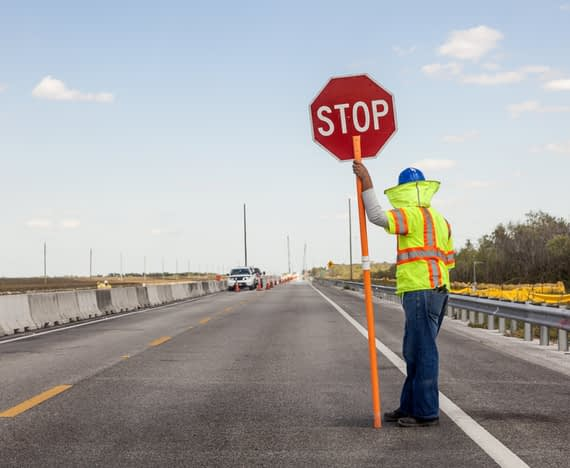 construction worker holds stop sign on roadway