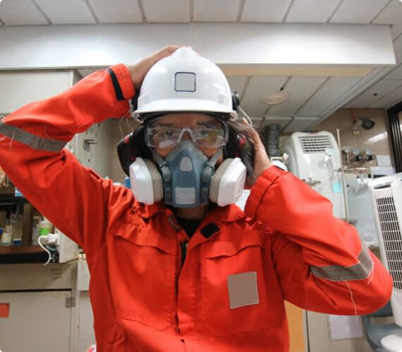 An environmental inspector with goggles and a helmet puts on a respirator