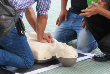 Two employees are instructed on how to properly perform CPR on a dummy