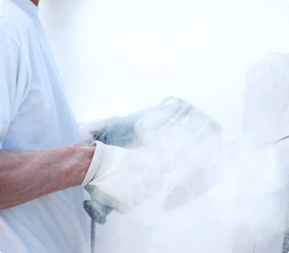 A man operates a circular saw as a cloud of ultrafine particles surrounds him