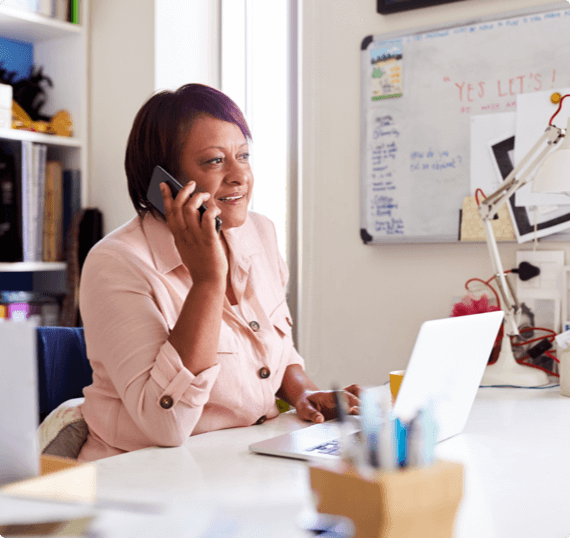 A woman speaks on the phone at her ergonomic desk