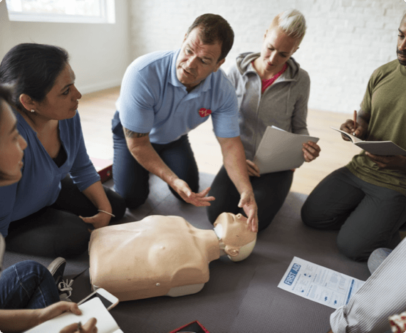 A health and safety instructor teaches CPR on a practice dummy