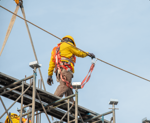 A construction worker walks on scaffolding wearing a safety harness