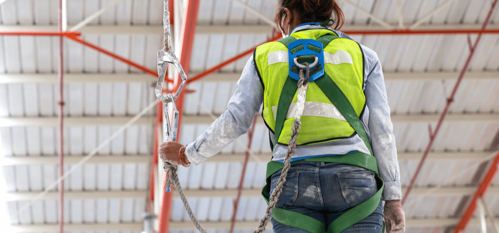 A worker wears a safety harness during a fall protection training session