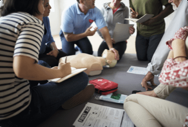 Employees take notes as they are instructed on how to perform first aid and CPR