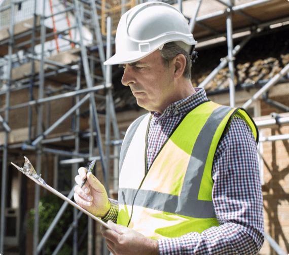 A safety inspector takes notes with scaffolding in th ebackground