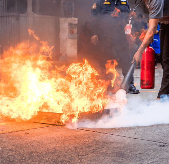 An employee puts out a fire with a fire extinguisher