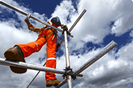 A worker stands high up on scaffolding after completing a worker safety awareness course