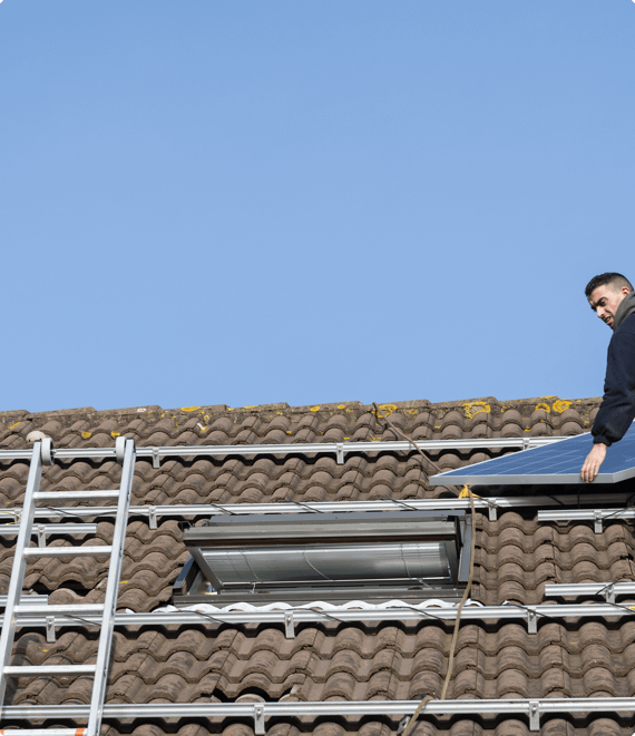 A man standing on the roof of a home