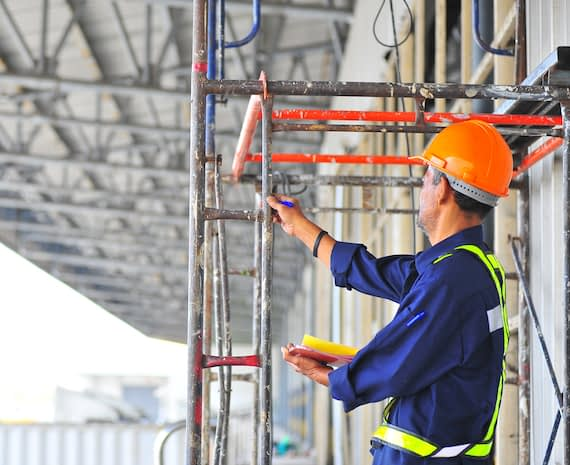 A man inspects the safety and stability of scaffolding