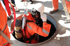 A worker being lowered into a confined space after doing their online training