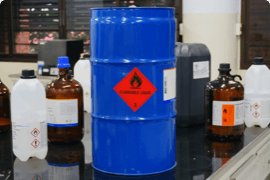 A blue barrel and several plastic containers of liquids marked with WHIMIS symbols
